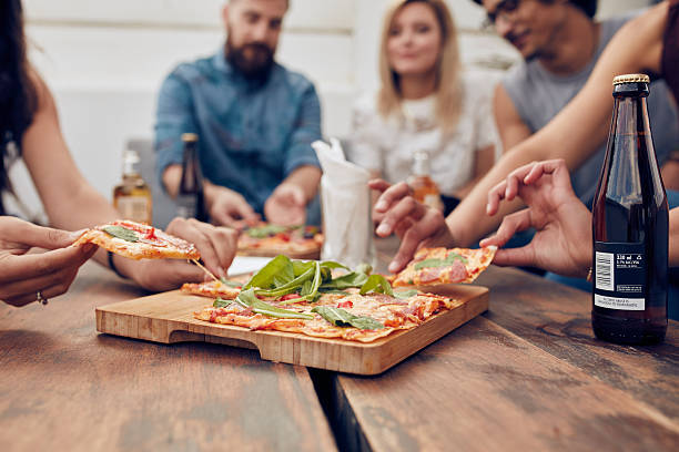 Friends partying and eating pizza stock photo