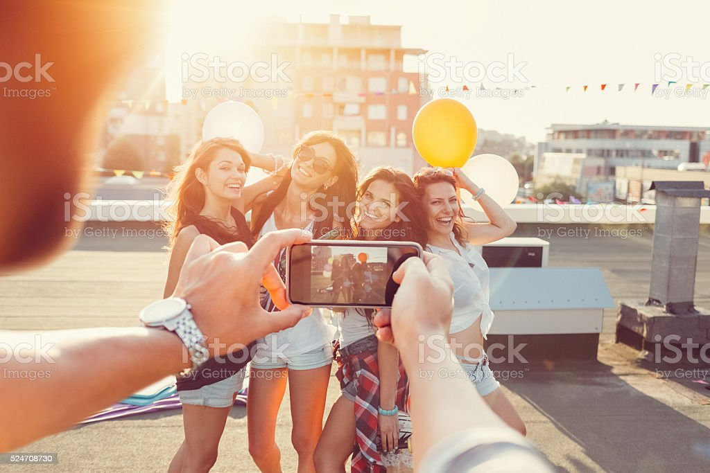 Friends partying on a rooftop terrace stock photo