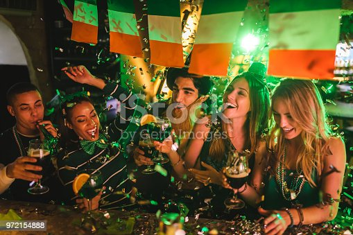 Happy multi-ethnic friends drinking and having fun at Saint Patrick's day night club party