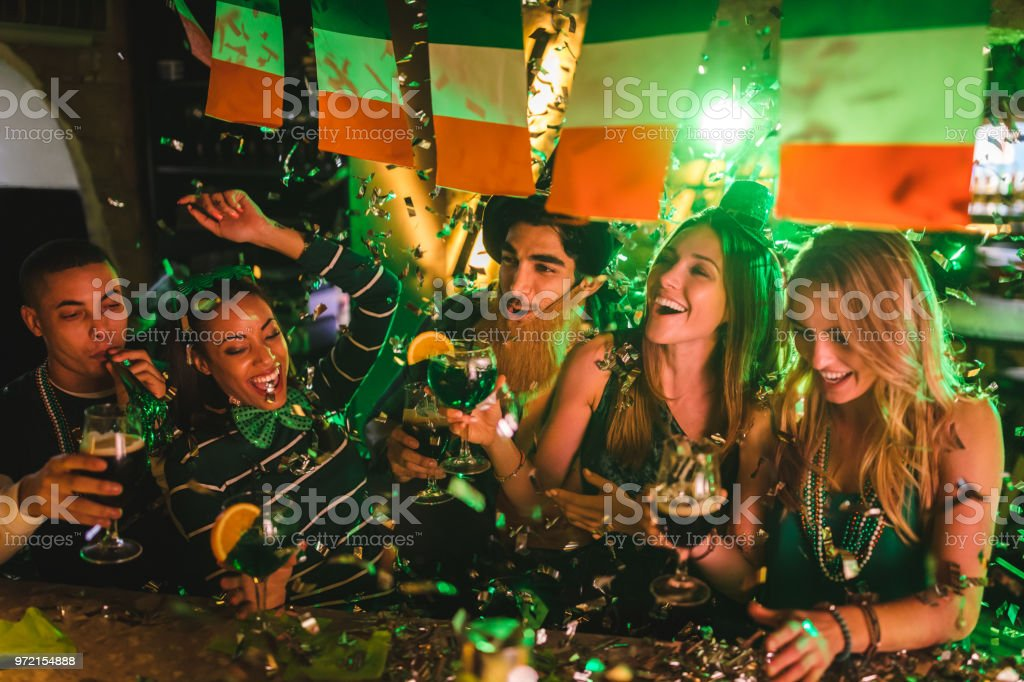 Friends partying with drinks and confetti on Saint Patrick's day stock photo