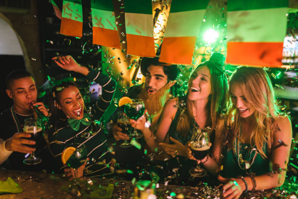 friends partying with drinks and confetti on saint patrick's day - st patricks day stock photos and pictures