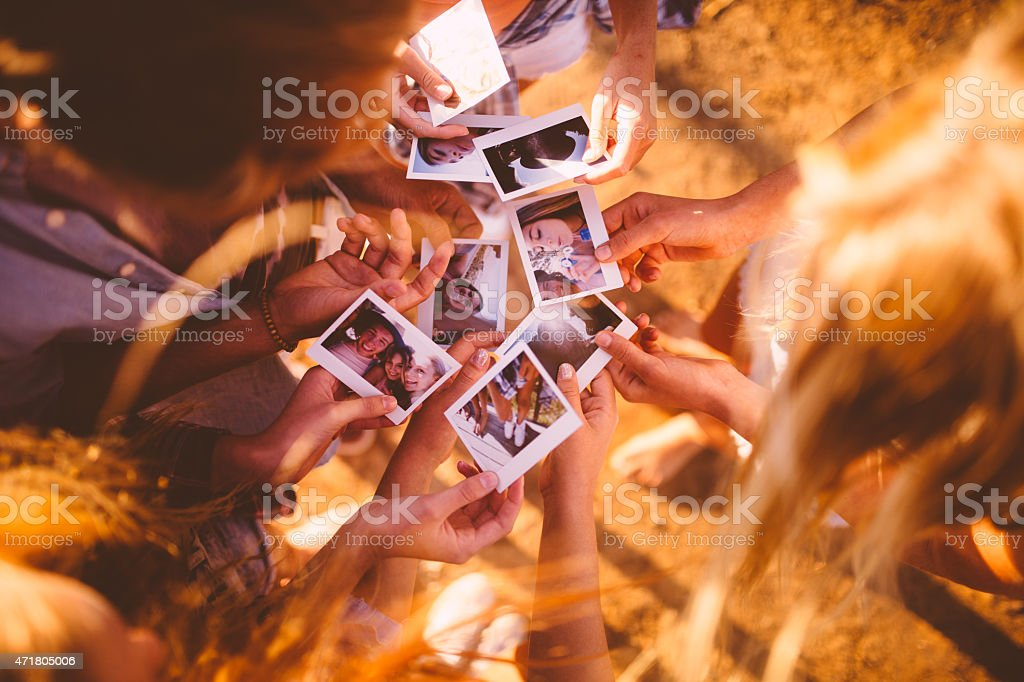 Friends passing round photos of themselves outdoors stock photo