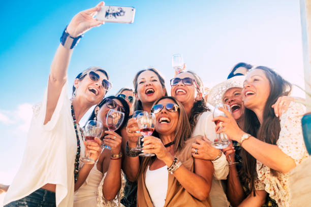 Friends people in group have fun together in friendship celebration party with red wine and selfie picture from phone - joy and happiness for young and senior women - blue sky in background stock photo