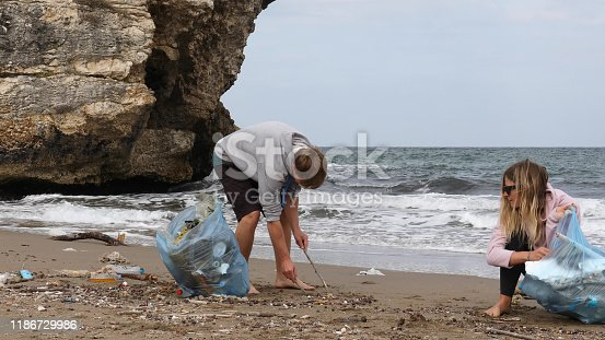 962184460 istock photo Friends pick up garbage on beach 1186729986