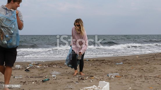 962184460 istock photo Friends pick up garbage on beach 1186730982