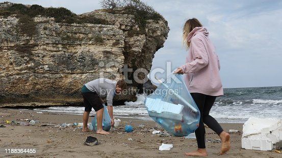 962184460 istock photo Friends pick up garbage on beach 1188364455