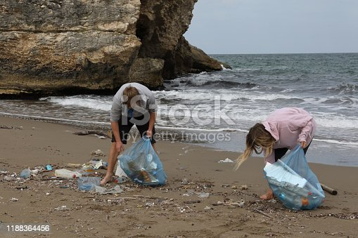 962184460 istock photo Friends pick up garbage on beach 1188364456
