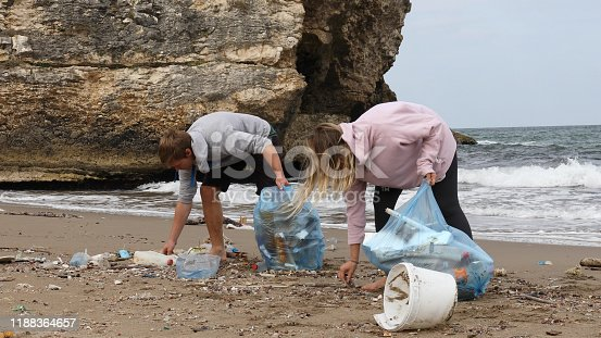 962184460 istock photo Friends pick up garbage on beach 1188364657