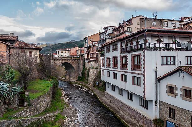 Potes View of the main bridge of Potes in Cantabria. This view is from a smaller bridge down the river made out of stone as well. cantabria stock pictures, royalty-free photos & images