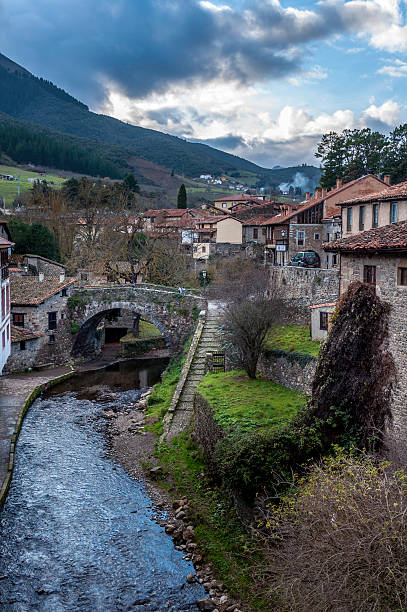 Potes Potes, Spain - December 29, 2011: View of an old stone bridge Potes in Cantabria. The old bridge is still in use as people can be seen crossing it. The mountains in the back is the Cordillera Cantabrica. cantabria stock pictures, royalty-free photos & images