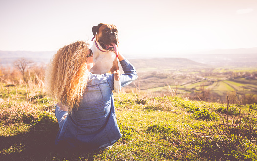 Woman with a boxer enjoying a beautiful day outside
