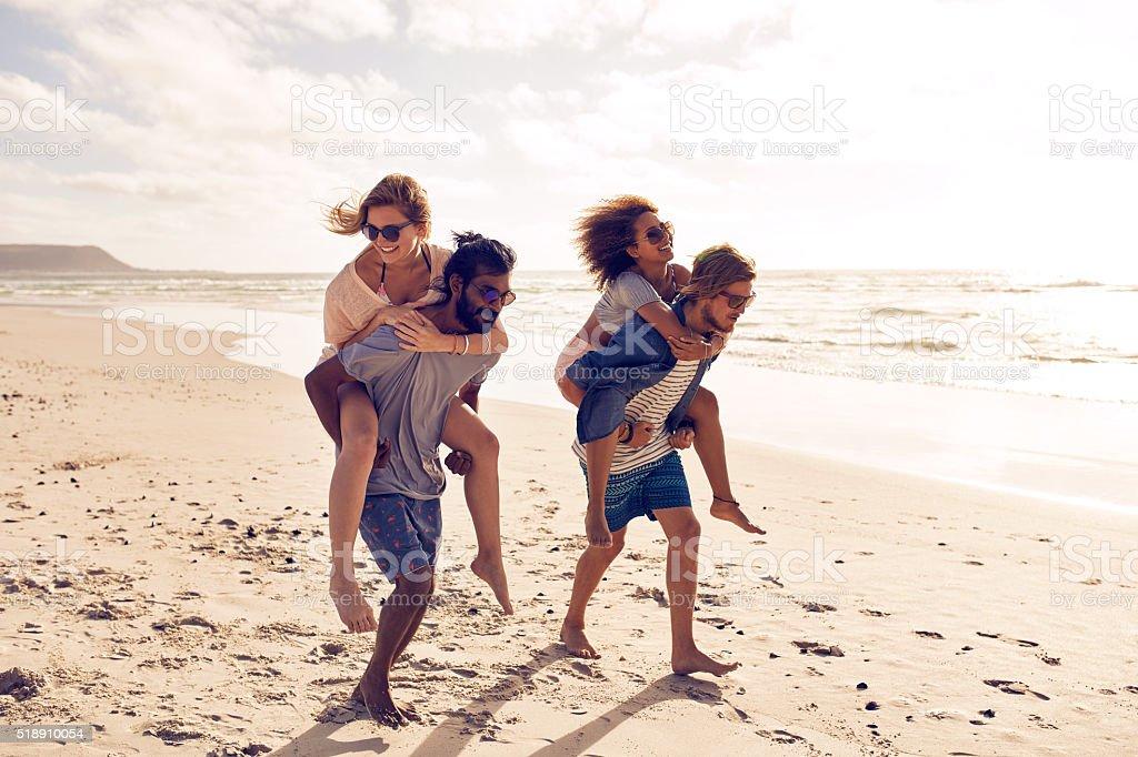 Friends piggyback along the beach stock photo