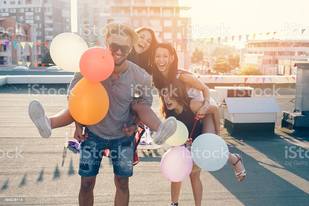 Friends piggyback on the rooftop stock photo