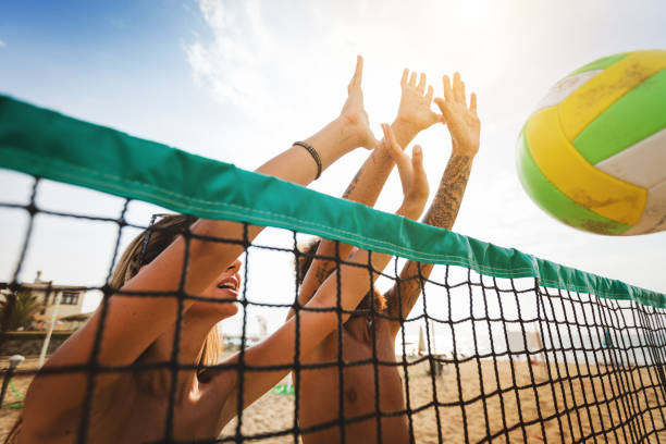 Friends play beach volley: defensive wall stock photo