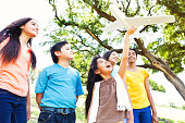 African American and Hispanic preteen, teen and elementary age friends play in the park together.  A little Hispanic girl holds a model airplain as her friends wathc. They are standing underneath a large tree.