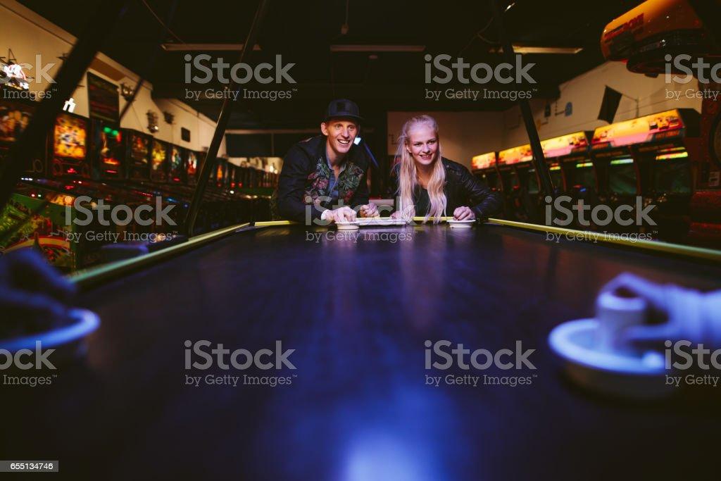 Amigos jogando uma partida de hóquei de ar - foto de acervo