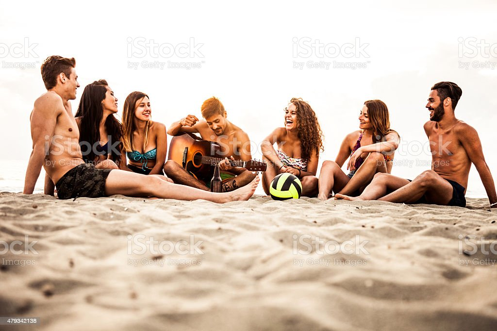 Friends playing and singing on the beach stock photo