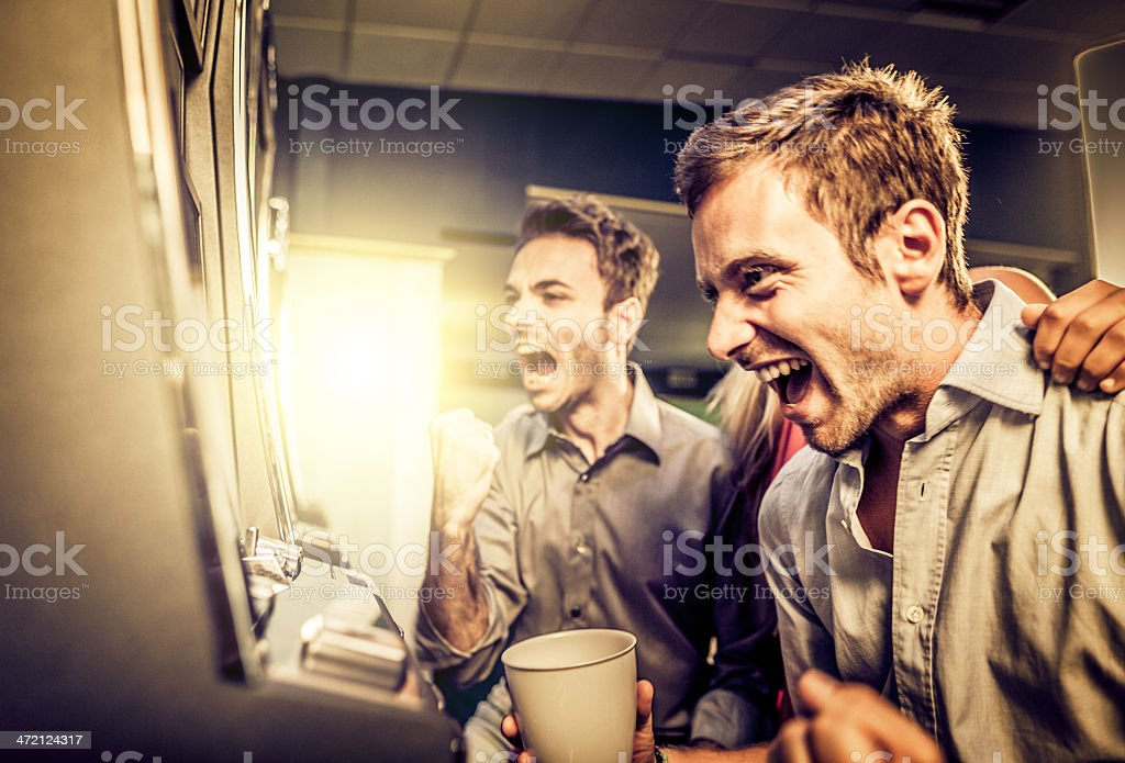 Friends playing and winning slot machine at casino stock photo