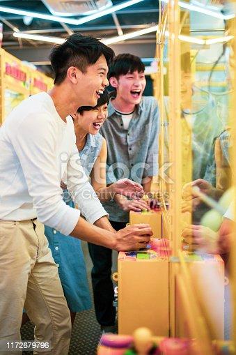 Friends playing arcade claw machine
