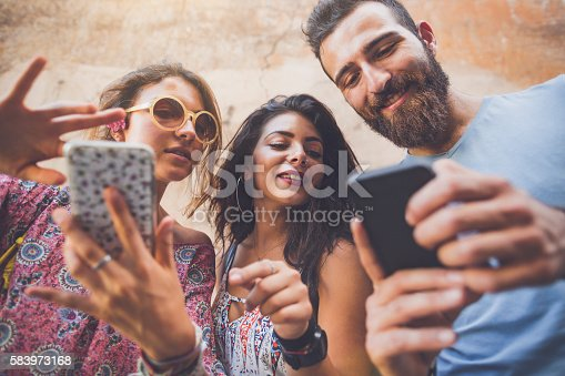 istock Friends playing augmented reality mobile game 583973168