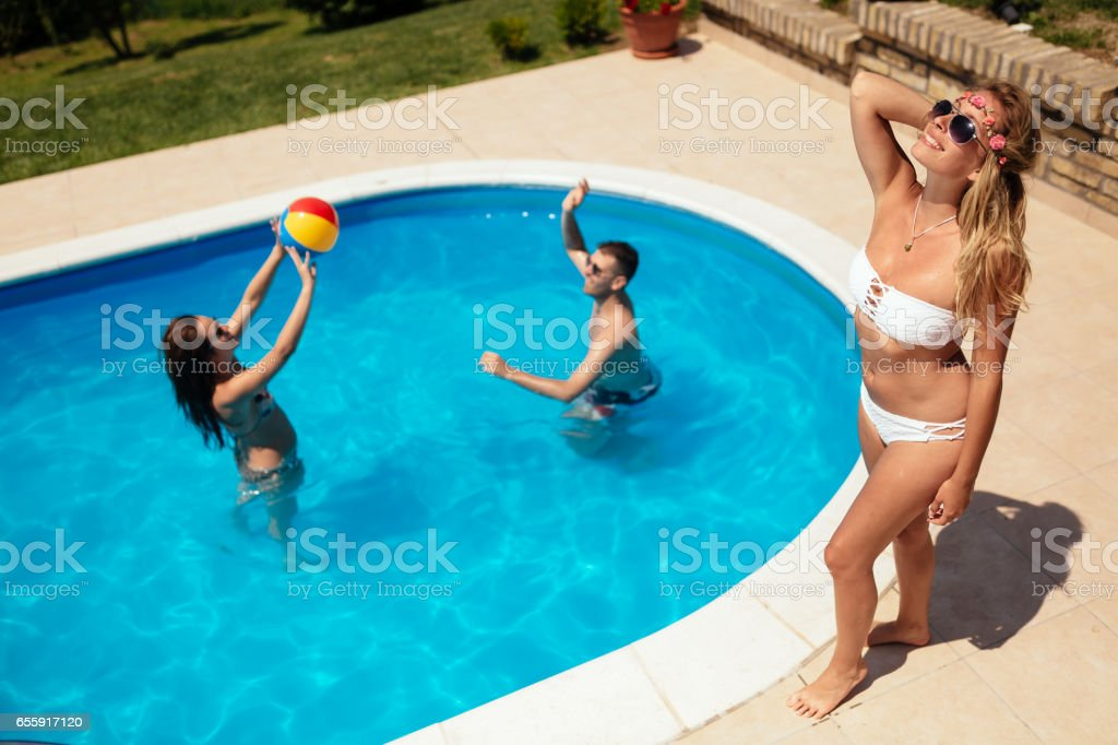 Friends playing ball games in swimming pool stock photo