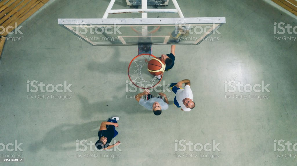 Friends Playing Basketball in a school gym royalty-free stock photo