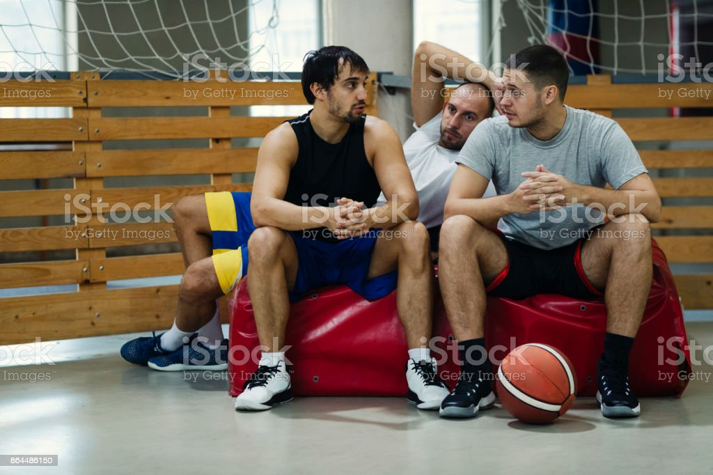 Friends Playing Basketball in a school gym. They are resting after...