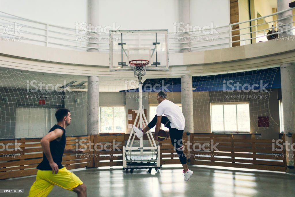 Friends Playing Basketball in a school gym stock photo