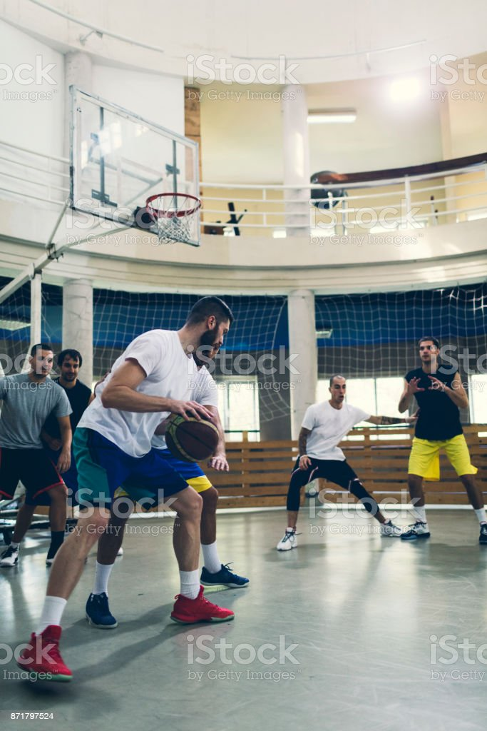 Friends Playing Basketball in a school gym. One player driblling the...