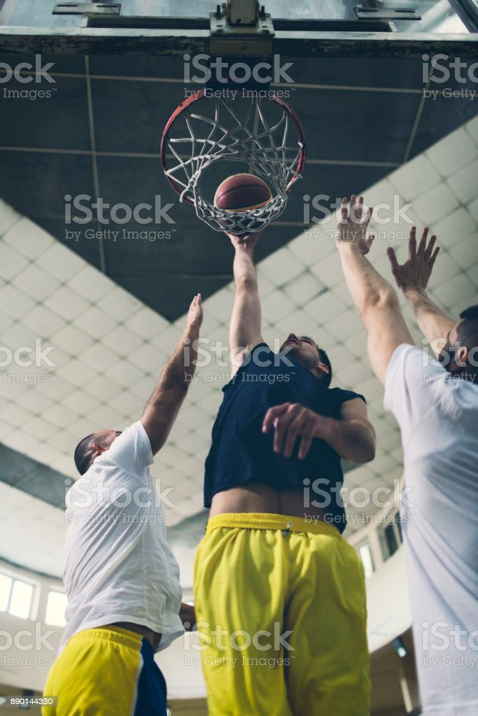 Friends Playing Basketball in a school gym. One player about to do...