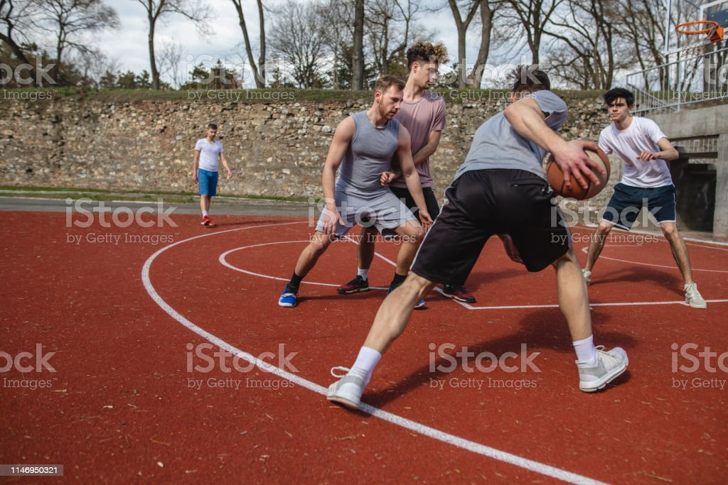 Group of friends playing basketball in two teams at a basketball court