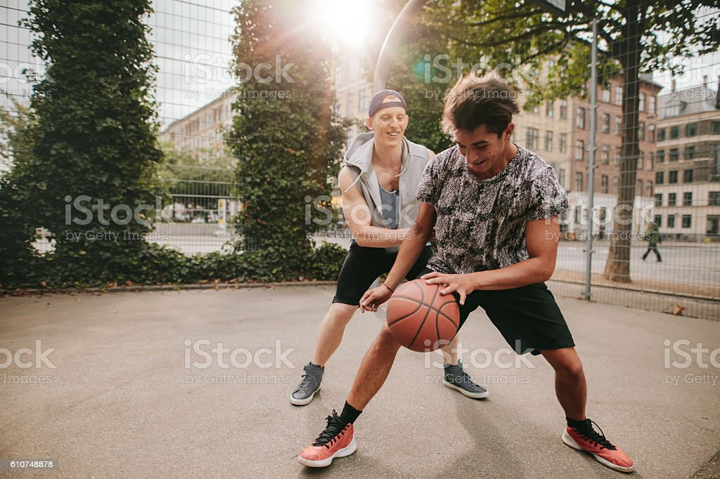 Friends playing basketball on court and having fun stock photo