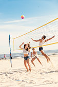 Group of friends, women and men, are playing beach volleyball.