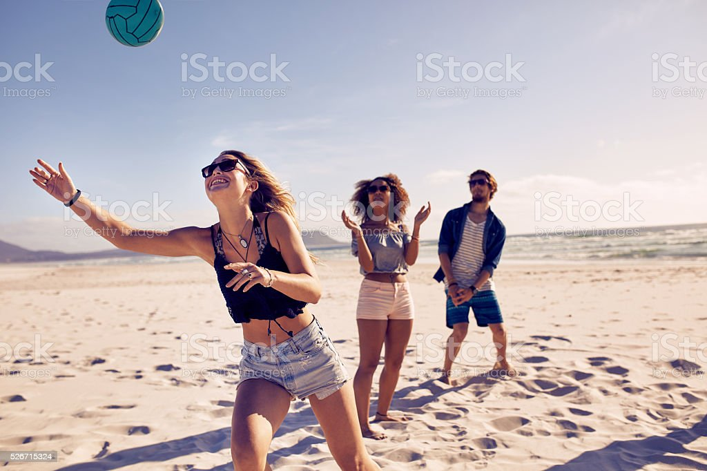 Friends playing beach volleyball​​​ foto