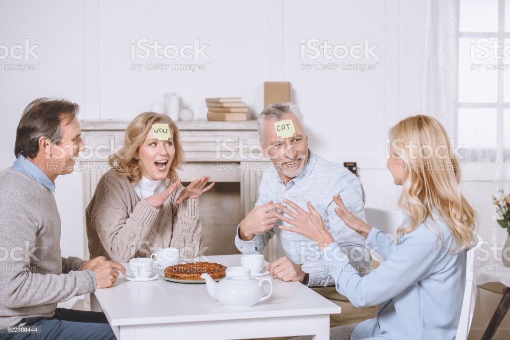friends playing card game with words on foreheads while sitting at table stock photo