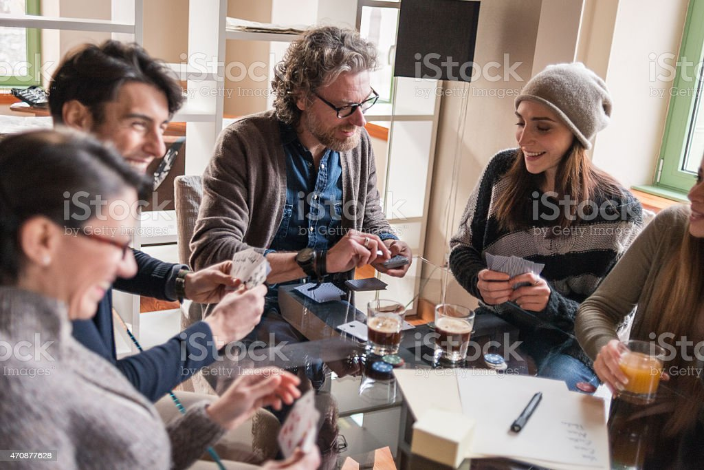 Friends playing cards and games, drinking in modern apartment stock photo