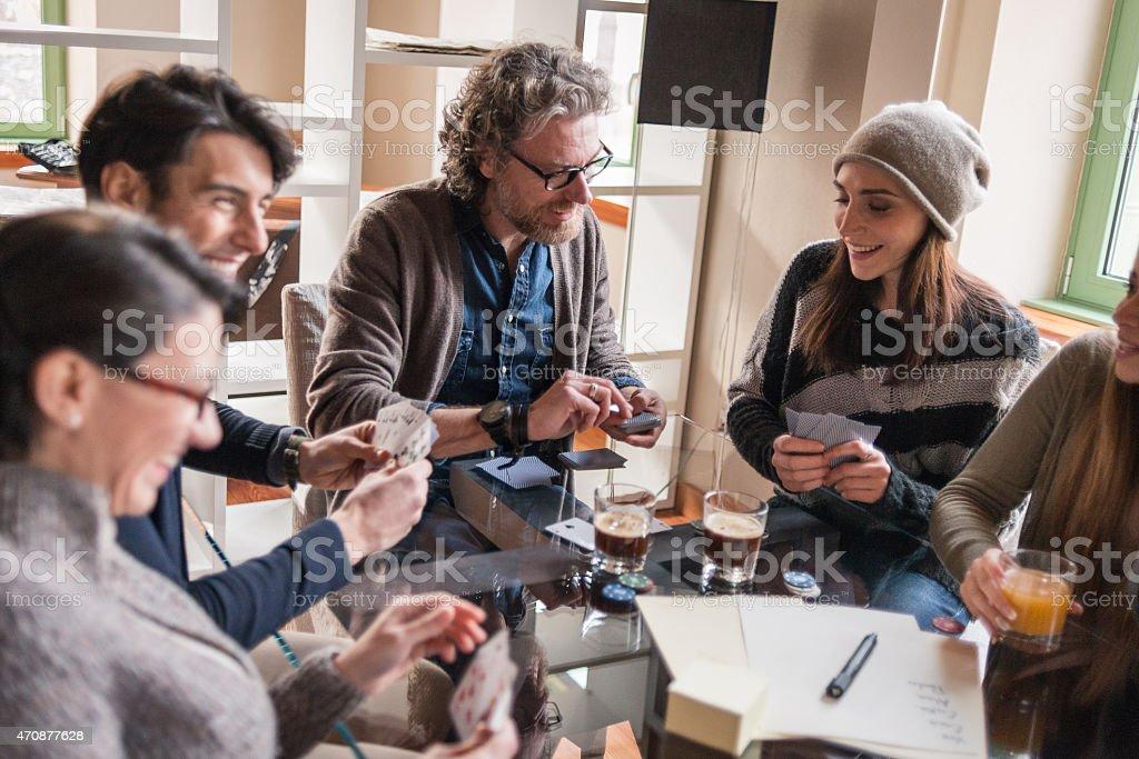 Amis jouer aux cartes et des Jeux à boire dans appartement moderne - Photo