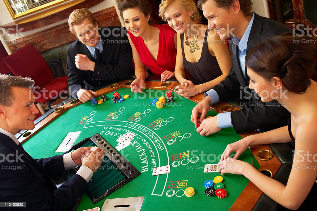 Friends playing cards on blackjack table stock photo
