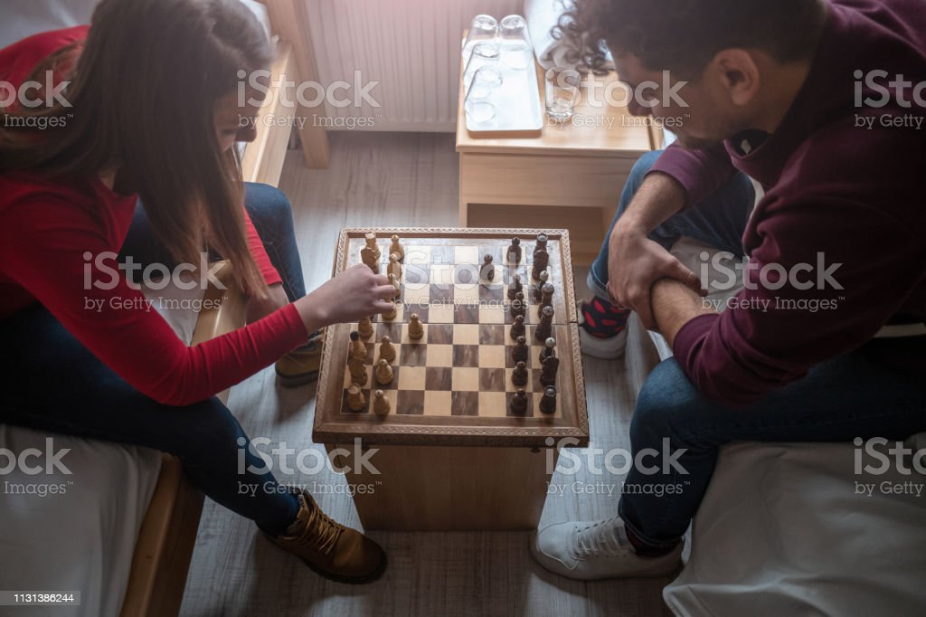 Friends Playing Chess In The Hostel Room Stock Photo - Download Image Now