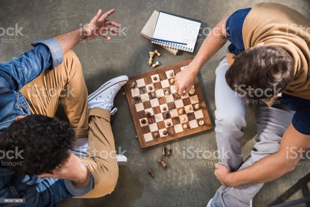 friends playing chess stock photo