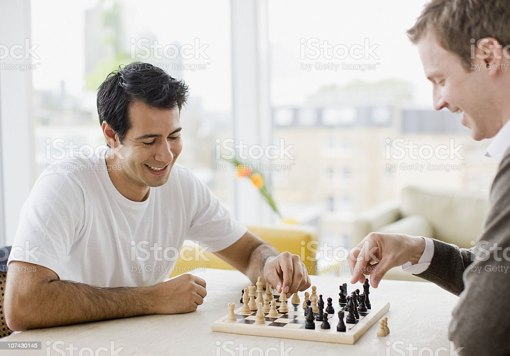 Friends playing chess together stock photo