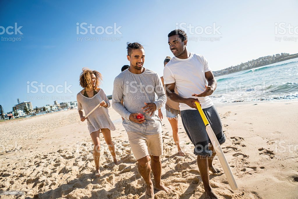 Friends playing cricket at the beach stock photo