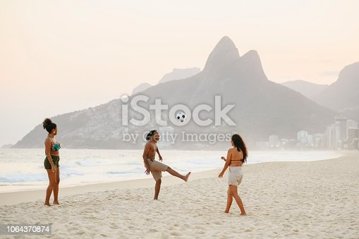 Three people kicking ball by water's edge on sandy beach at dusk with Two Brothers mountain in background