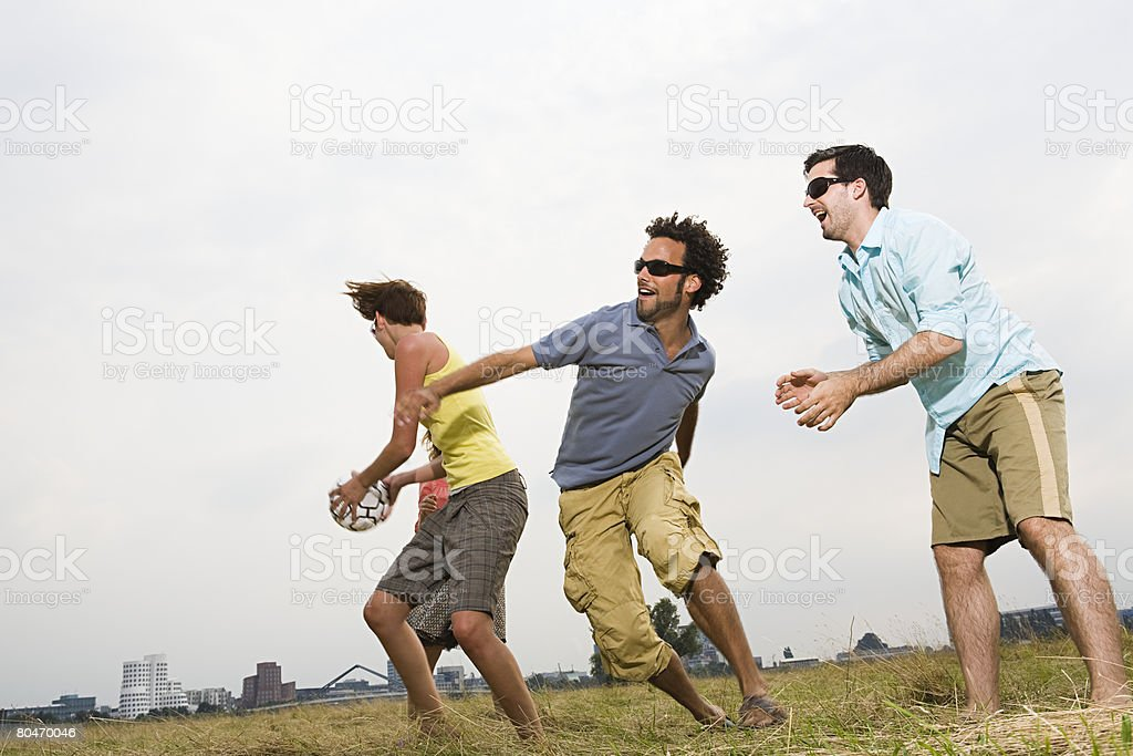 Friends playing football royalty-free stock photo