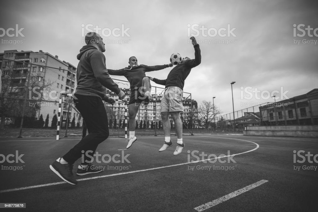 Friends playing football stock photo