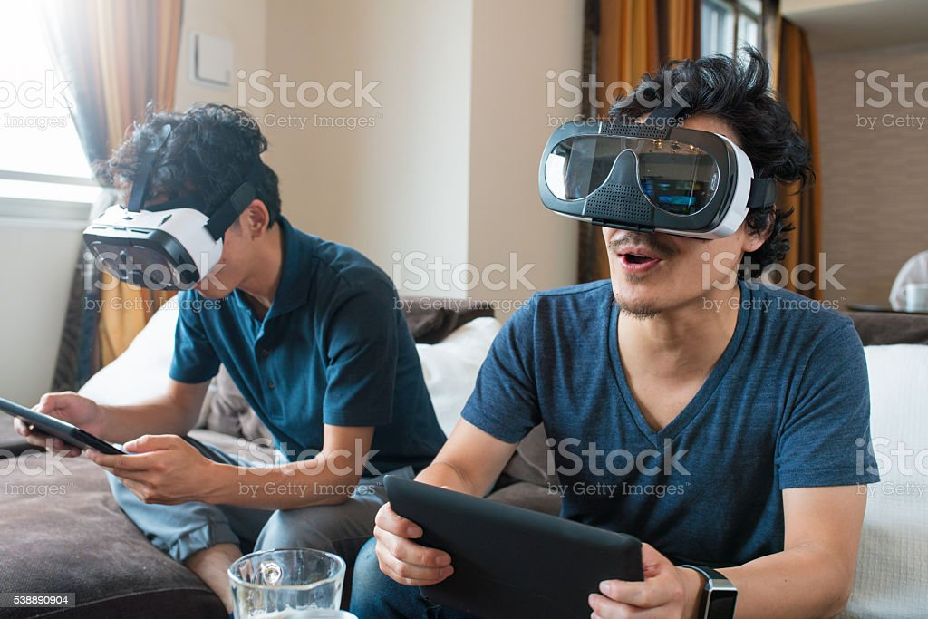 Friends playing games using virtual reality headsets stock photo