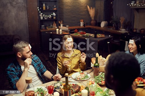 Multi-ethnic group of young people playing guessing game while sitting at table during dinner party in dark room, copy space