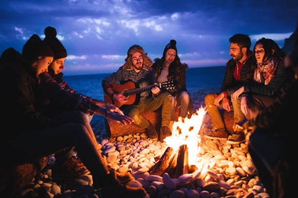Friends playing guitar and singing around bonfire at the beach Young hipster friends with a guitar singing around a campfire at a beach at dusk bonfire stock pictures, royalty-free photos & images