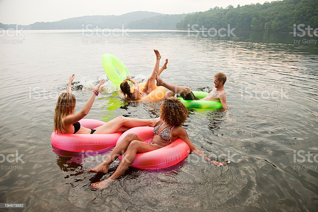 Friends playing in inflatable rings on lake stock photo
