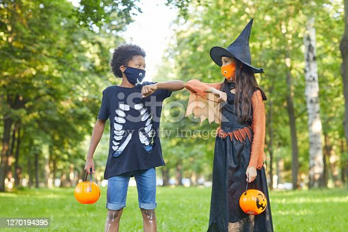 Two friends in Halloween costumes playing with each other in the park